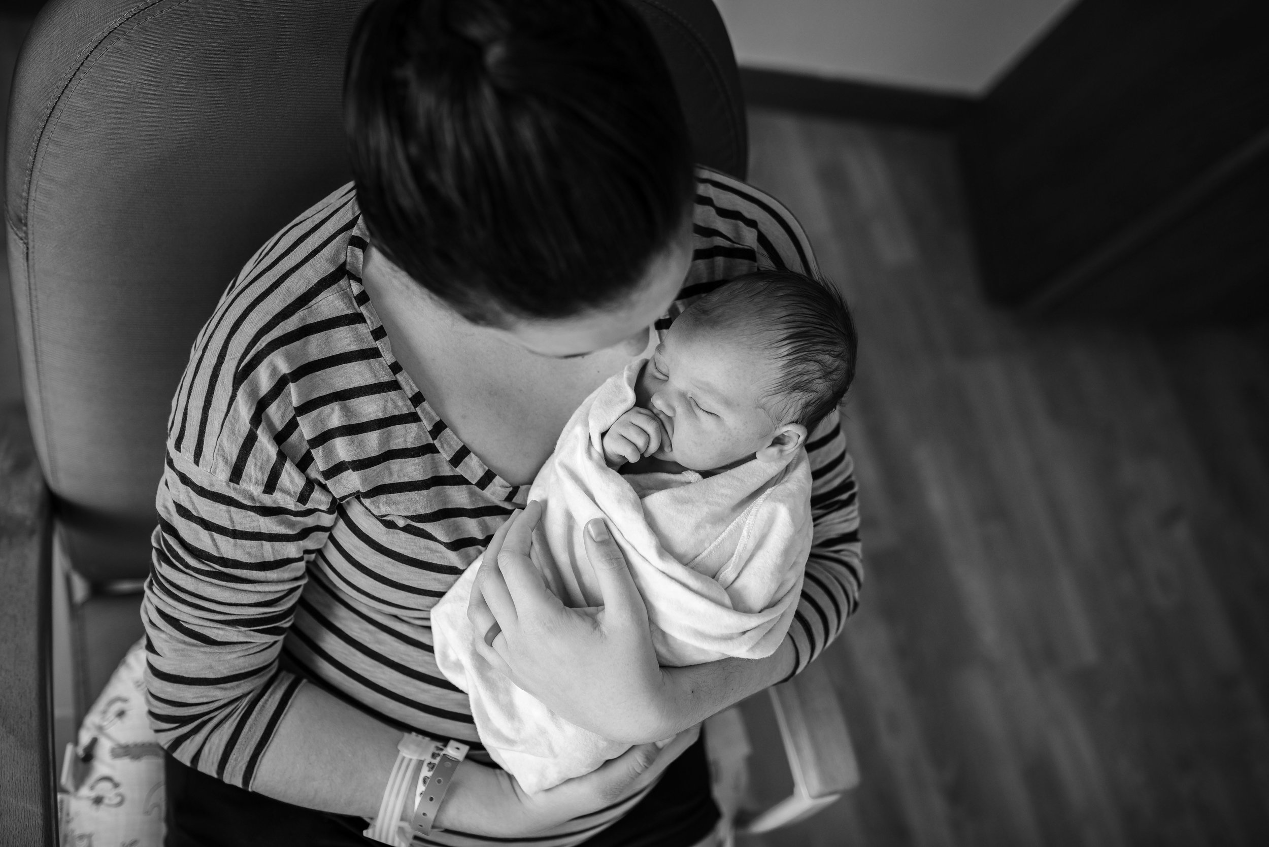 Black and white image of mother holding her newborn daughter after their hospital birth in Jacksonville, Florida.