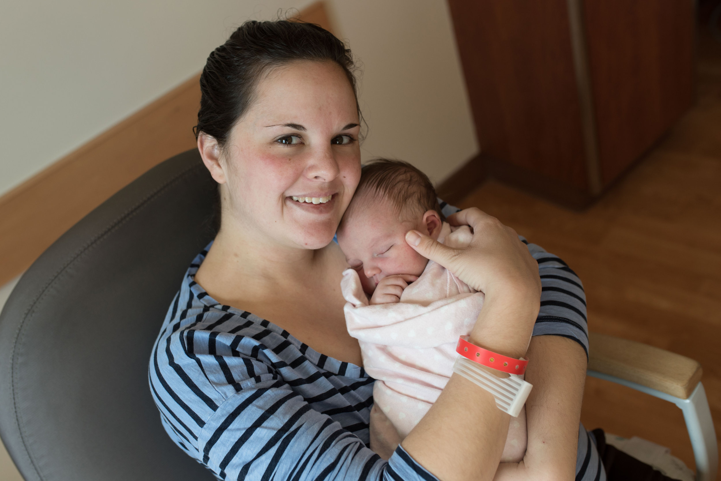 Smiling mother holds her newborn baby for a hospital photo session in Jacksonville, Florida.