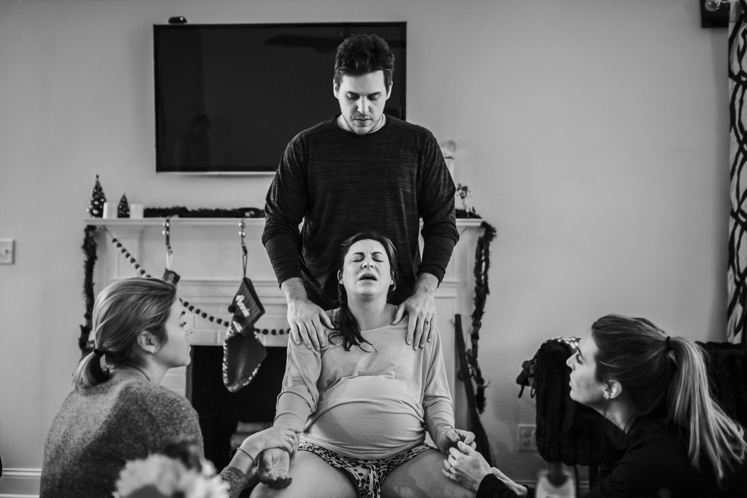 Laboring mom is supported through a contraction by her husband and sisters.