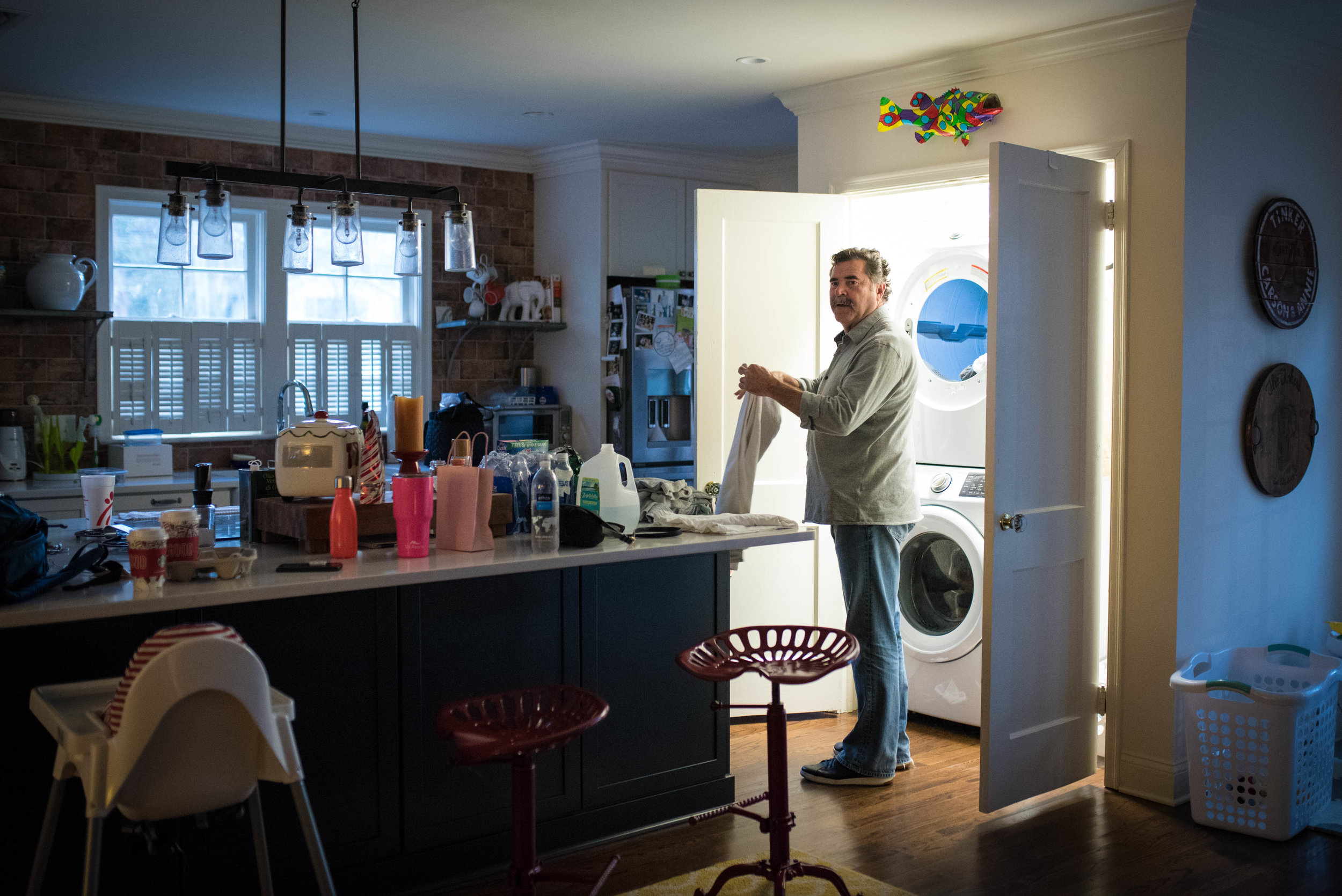 Grandpa looks on and folds laundry while his daughter labors at home.