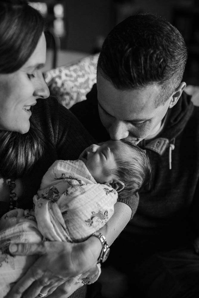 Dad kisses the head of his newborn son in a lifestyle newborn photography photo session.