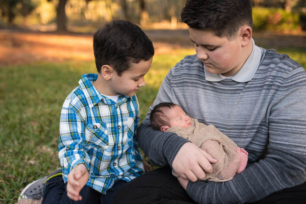 Big brothers look at their newborn baby brother during a lifestyle newborn photography session.