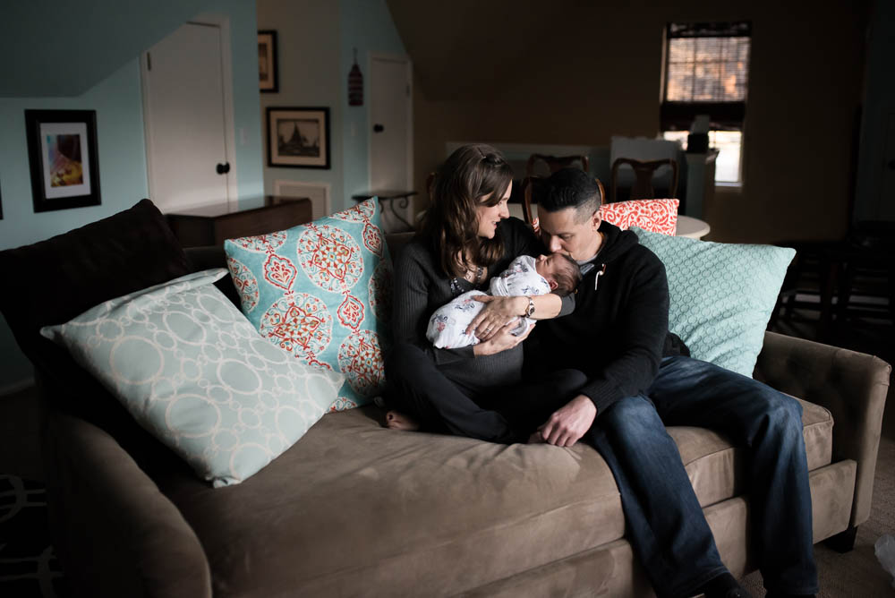 Jacksonville couple holds their newborn baby during a lifestyle newborn photography session.