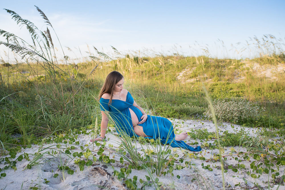 Mom rests at the beach while she poses for a photo. She is pregnant with her first baby and in her third trimester.