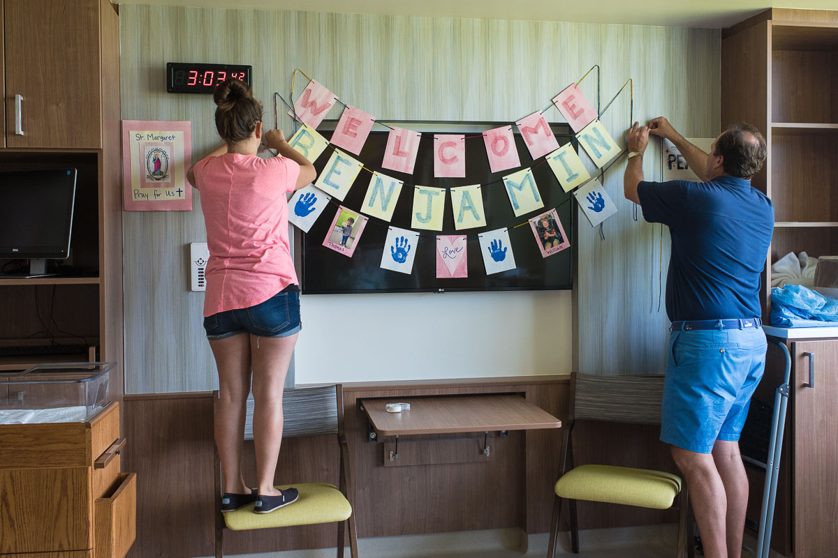 A doula helps her client's husband to hang a homemade banner in her labor and delivery room at UF Health North. They decorated the hospital room with pictures of her other children.