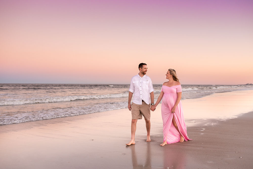 A couple walks along the ocean at a beach in Jacksonville, Florida with their maternity photographer. They are having their first baby at the UF Birth Center.