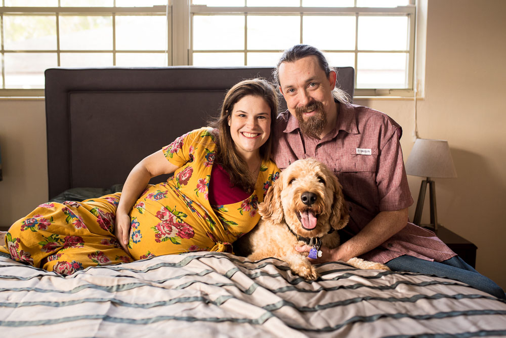 A husband and wife pregnant with their first baby snuggle in bed with their dog.