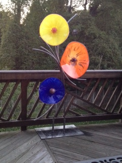 On your deck what a great spot for your new glass flower sculpture look out every window and see these 18″ glass flowers all year long bright cobalt, bright orange and vivid yellow.this piece stands 72″