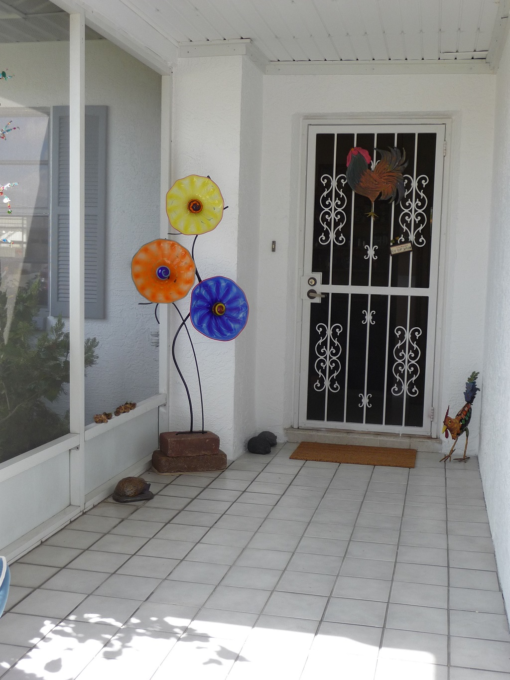 Free standing glass flower sculpture is shown on their porch at the entrance to their home no better way to greet your guests and make them feel welcome. colors shown are cobalt, yellow and orange. This piece is 66″.