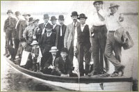 Many special occasions such as Midsummer's Day and Syttende Mai (May 17th, Norwegian Independence Day), were celebrated to preserve ethnic traditions. On special outings, miners often dressed in their best suits as shown in this photo they posed in a sailboat on Rabbit Lake.