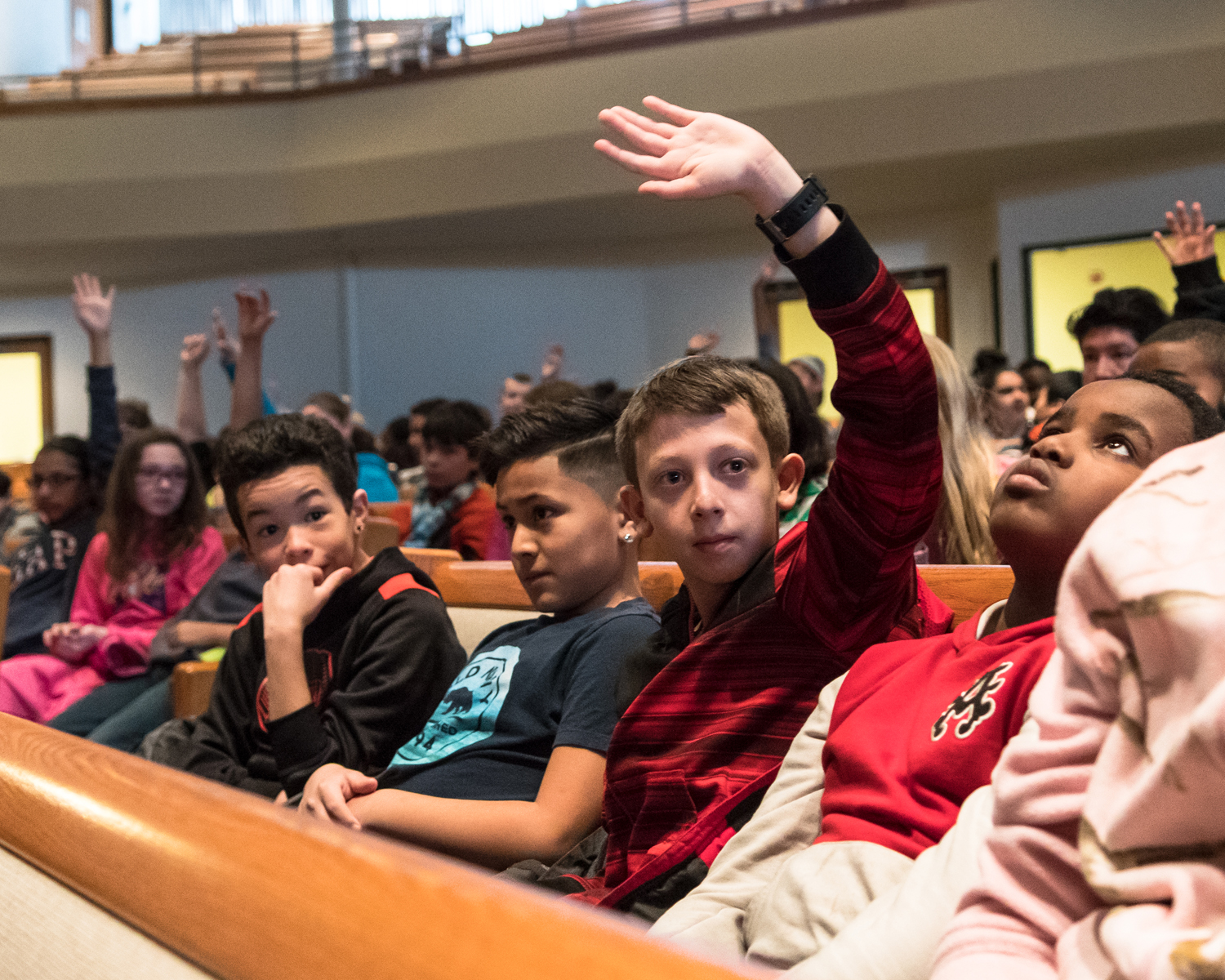 Fifth-grader John Rodgers, an aspiring trombone player from Wadewitz Elementary School, raises his hand when brass instrument players are called on by the Racine Symphony Orchestra conductor Pasquale Laurino during the RSO's Concert for Fifth Graders on Tuesday, March 14, at Grace Church in Caledonia