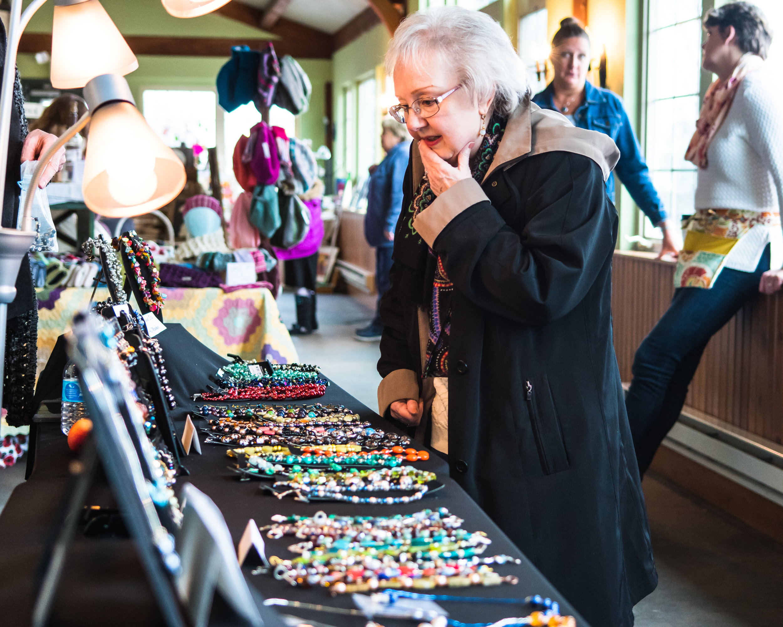 Decisions, Decisions--Karen Buswell looks over the jewelry selection of Linda Glass, of Designs by Glass, during the Spring Arts & Craft Fair at Borzynski's Farm and Floral Market, 11600 Washington Ave., Mount Pleasant, on Sunday.