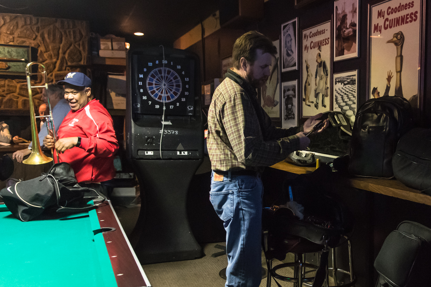Dave Ferguson, Trombone, and Garrett Kornman, Alto Saxophone player, unpack their instruments around the pool table of McAuliffe's Pub for The Parkside Reunion Big Band's bi-weekly performance on April 4.