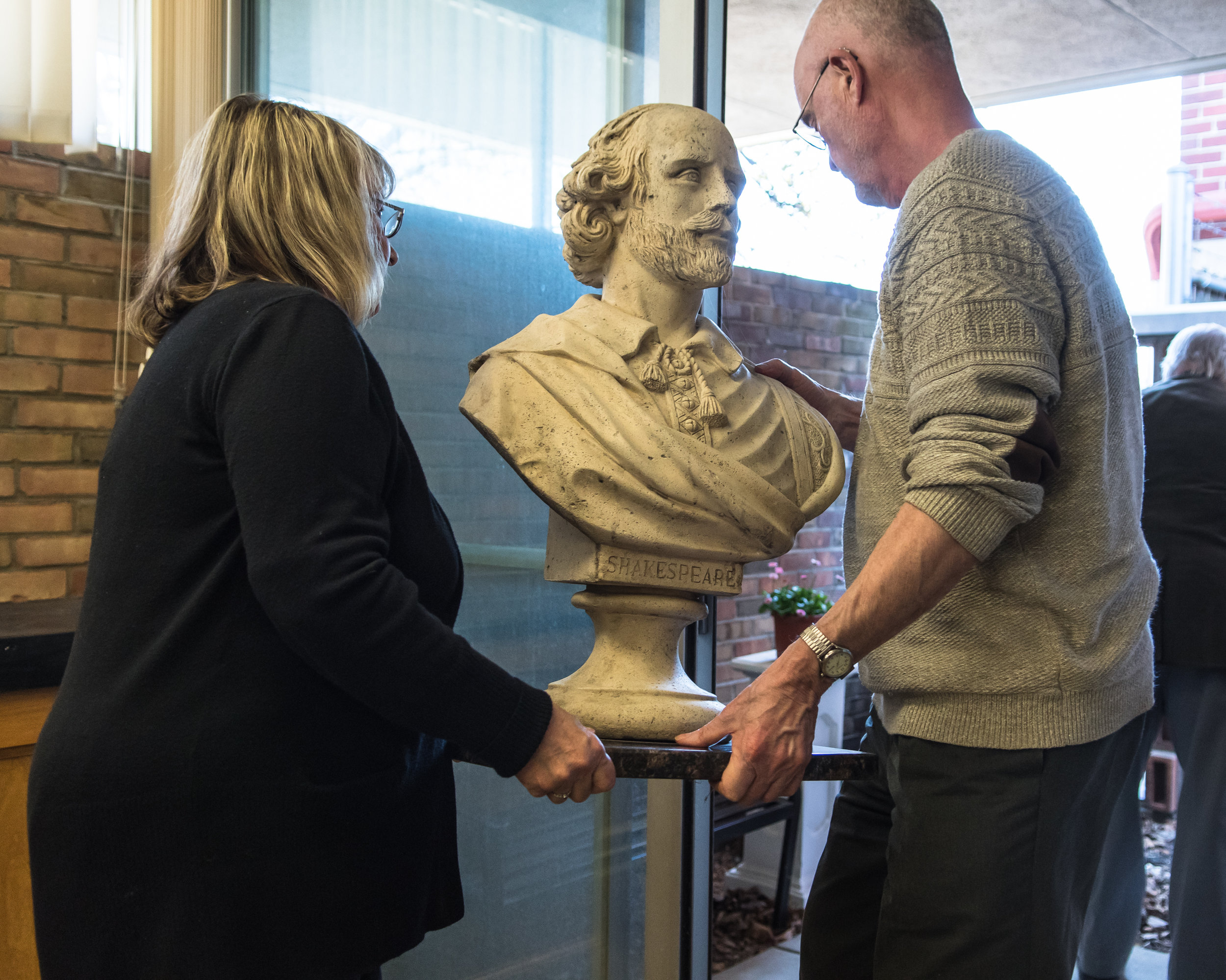 Kay Gregor of the Racine Literary Council and Jerry Belland ceremonially move a bust of Shakespeare outside to it's spot in the Audrey Onstad Shannon Memorial Poets Corner of the Racine Literary Council during their celebration for Shakespeare's Birthday on Sunday.