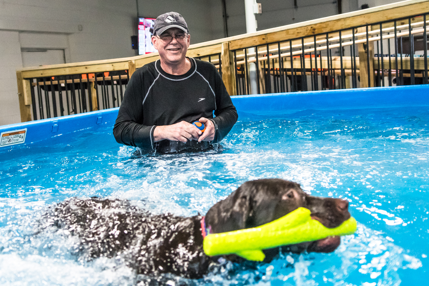 Owner of Club Aqua Paws in Downtown Racine Mike Iwon, Racine, monitors first time swimmer Tilly as she hones her newfound skills and beings playing with toys in the pool Thursday afternoon.
