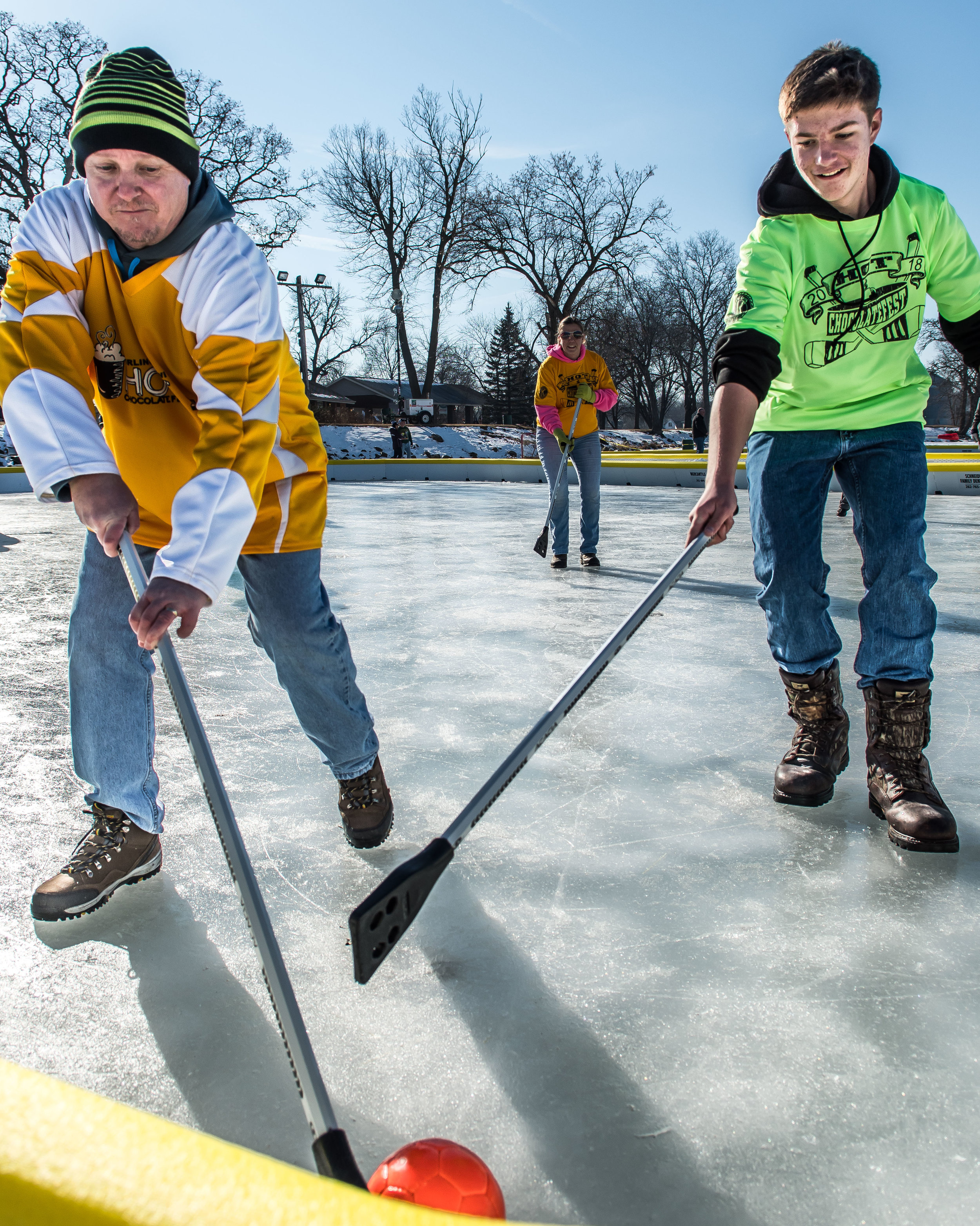 Jeff Van Lysal runs for the ball closely followed by Matthew Oliver, 14, during an adults versus kids game of Broom Ball on Echo Lake during Burlington's Hot Chocolatefest Saturday afternoon.