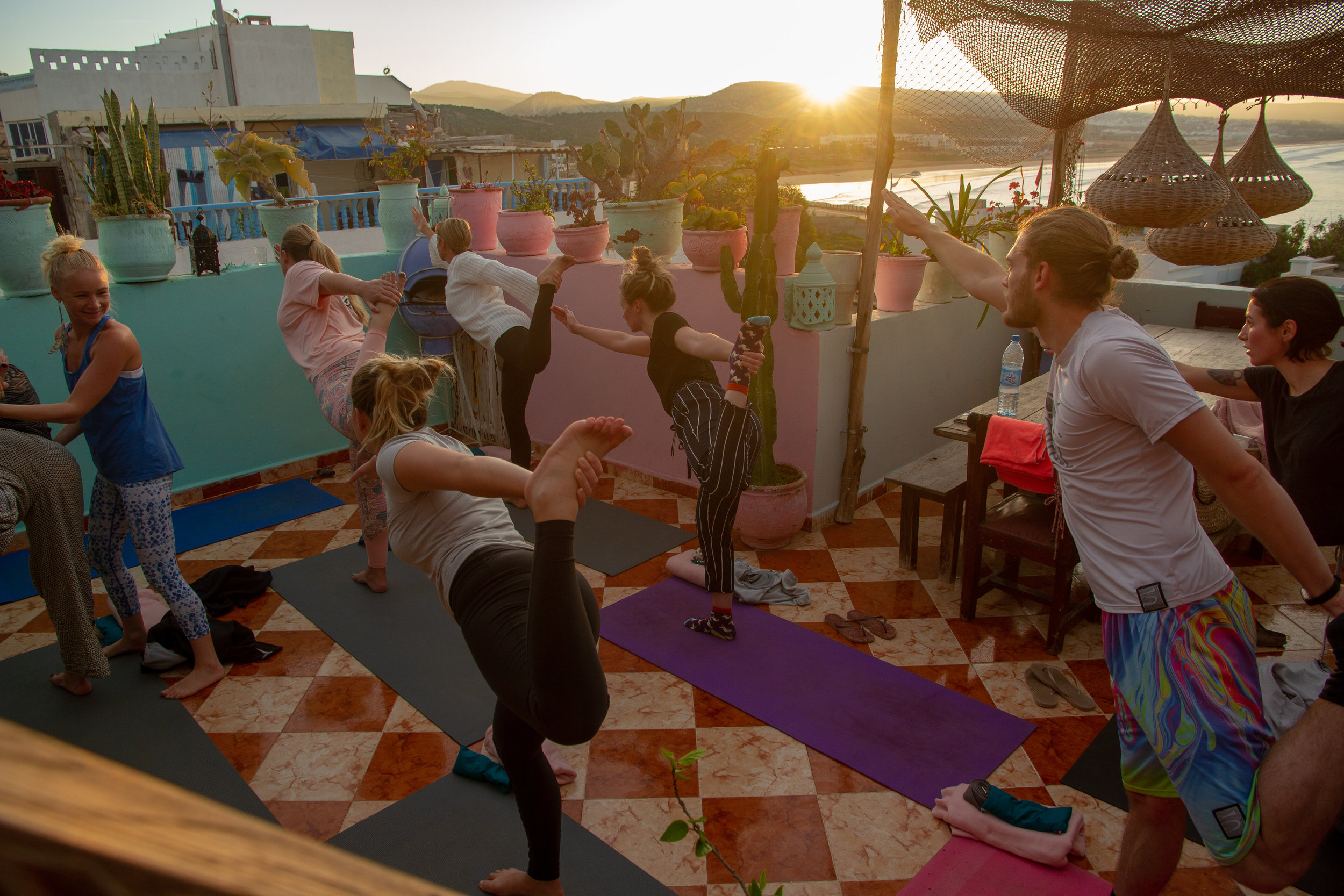 Sunrise over mountain and sea whilst group of people partake in yoga lesson on plant filled terrace