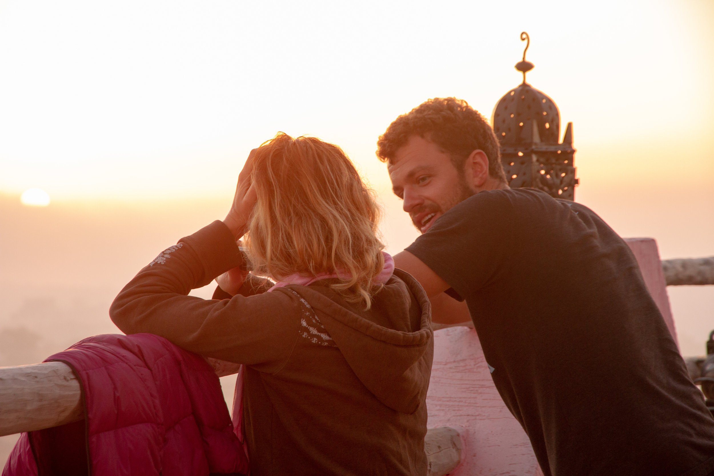 Couple chatting at sunset on a moroccan balcony