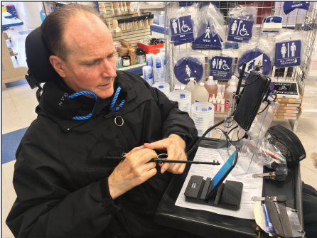 Kevin Giblin using his smartphone sitting on a Cradle Stand