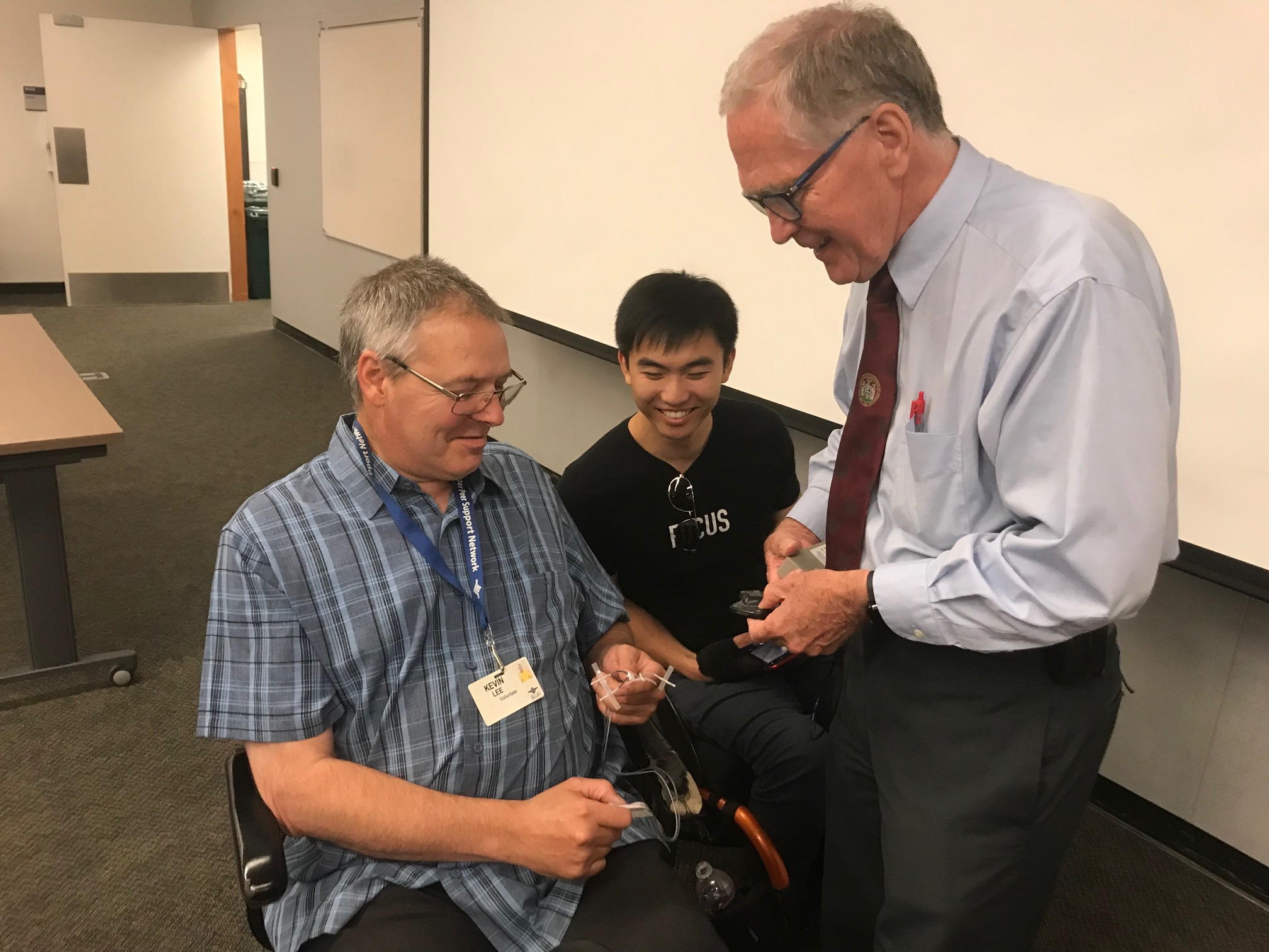 Dr. Creasey showing Kevin Lee (in front) and Ran Tao the electrodes used in the procedure.