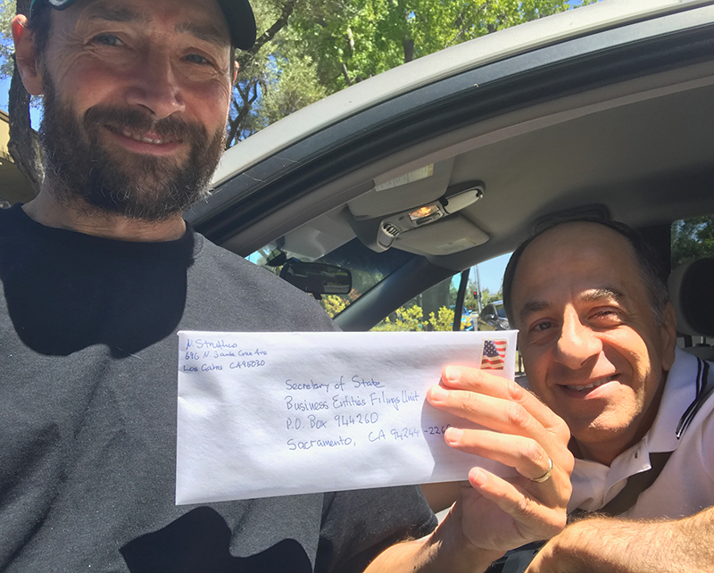 Nick holding up an envelope containing the registration of the foundation with the State of California prior to mailing it.