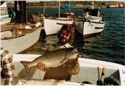 """Here's a younger, slimmer, hairier Tim circa 1986. Behind him is the """"Edgy"""" which was Tim and Margaret's first crab boat and the sailboat Whereaway which was their home for nine primitive years . Built in 1933 Edgy was originally a Japanese gillnetter. Note the Songhees shoreline in the back ground, devoid of the current condos and complete with Seaspan chip barges."""