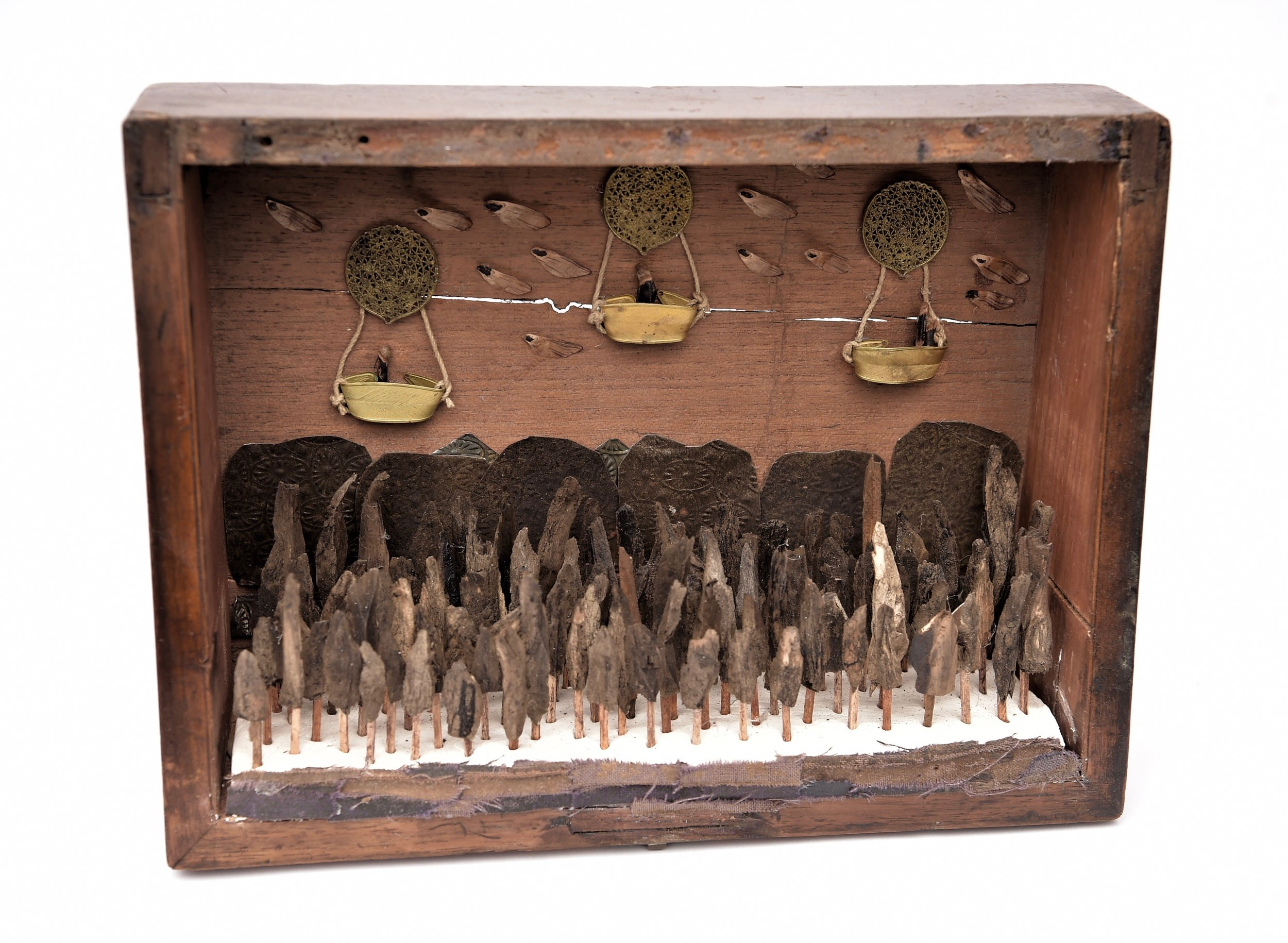 an old wooden box filled with broken bits of bark making up a forest. hot air balloons made out of found objects float above it.