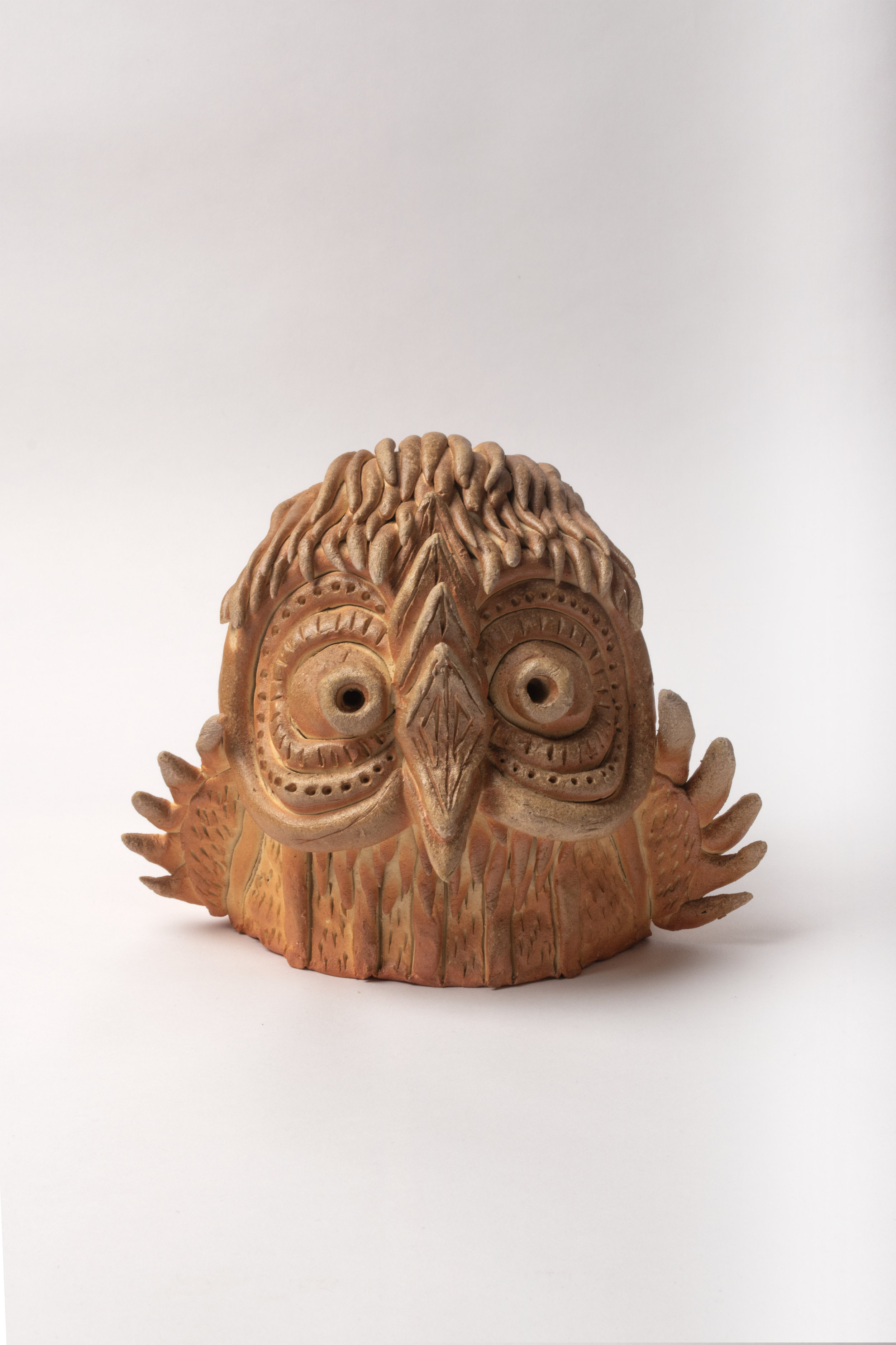 A soft looking pale brown ceramic owl head. big wides eyes and small wings sticking out the sides. small tail at the back and tubes of clay make up the surface texture one next to the other.