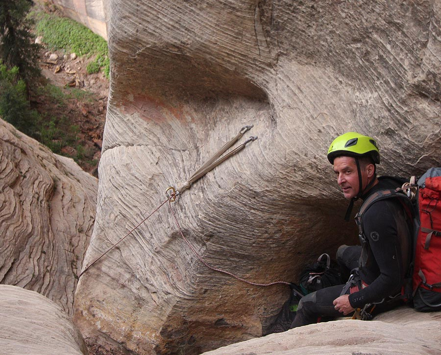 Nat Smale of Salt Lake City, our fourth, actually showing some color. Soon to be on rappel. Hmmm. I bet this is the rap where my rope got tweeked. That sling should really have been extended over the edge. (Zion)