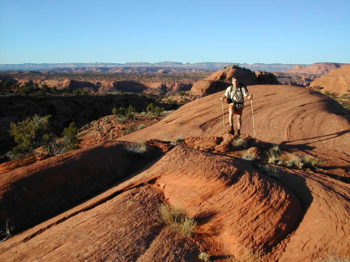 The Approach - From a camp near the mouth of Fence Canyon, cross the Escalante River and follow a trail on the other side up-canyon. Near where the trail first approaches the canyon wall, ascend an easy slickrock slab to the first bench and traverse northward. Work your way up until you are on the Overland Trail. Follow this north to the first side canyon, then follow the sidecanyon east to the benchlands above. Hike east, into the rising sun, across the top of one mesa. At the second mesa, cut left onto the shoulder of mesa 5776T. Find a 4th class chimney to get down the cliffbands and down to the slickrock benches. Continue east until it is possible to walk down into the bottom of the canyon.