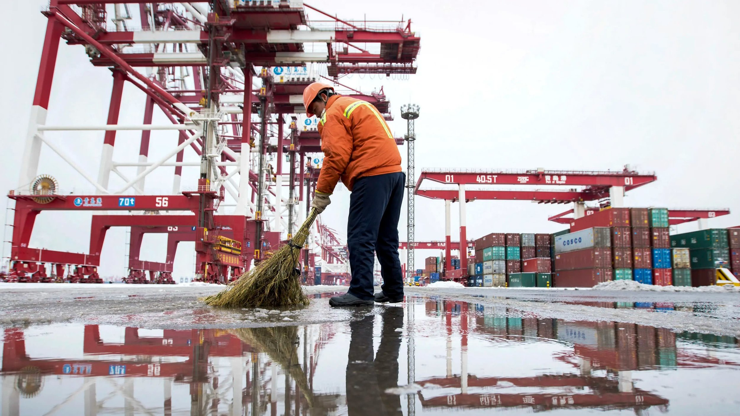 A worker sweeps the road at a container port in Qingdao in east China's Shandong Province. American and Chinese trade negotiators cannot agree on enforcement measures ahead of a trade deal. Photo credit: AP