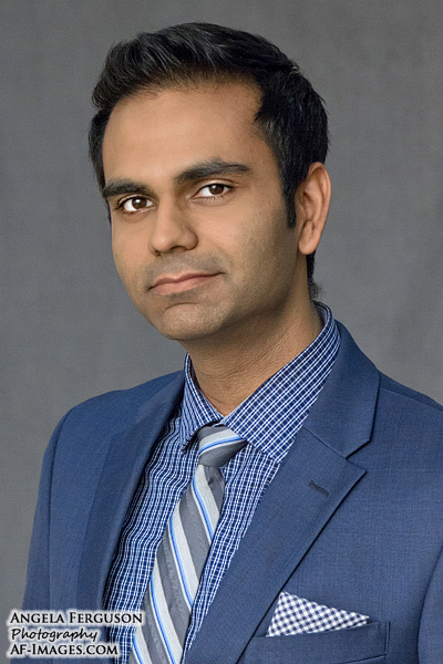 Man's business headshot, wearing a navy suit in front of a gray backdrop.