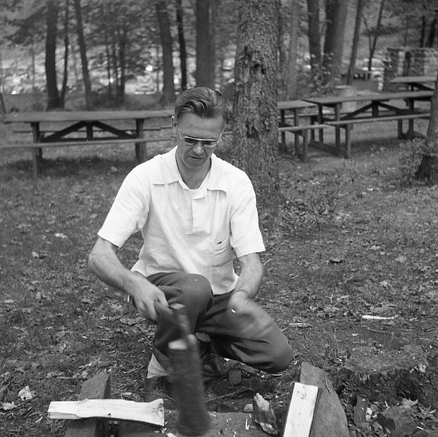 Rolie, splitting wood at a Kins Club picnic.