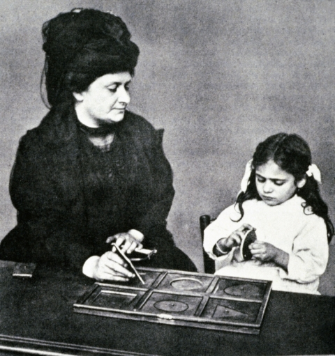 Dr. Maria Montessori modeling with a child how to use the metal insets, Early Children's House, Italy.