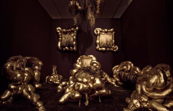 I approached Rashelle Roos's gilded parlor - of overstuffed arm (and leg) chairs. Set up like a theatrical tableau, Roos stuffs pantyhose to create bulbous anthropomorphic furniture—a life-sized chandelier, coffee table, paintings, sofa—laced with wigs and hair pieces. The result is a spectacle that repels and attracts. Its materials and surfaces invite a lingering gaze yet its intestinal abjectness prompt one to question who inhabits this domestic interior. The sagging, imperfect qualities of the forms nod to the aging process and perhaps the domicile of fallen beauty…. —Julie Rodrigues Widholm