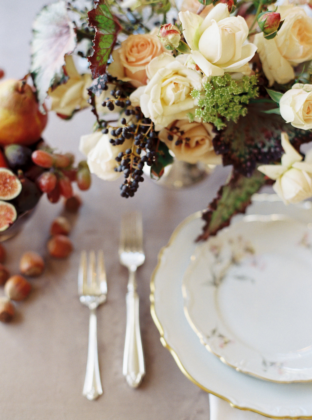 fall themed wedding table with fine china silver dates grapes and a white and peach bouquet