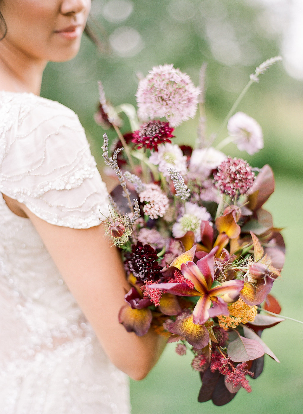 bride holding a pink and yellow bouquet in a beaded cap sleeved gown in winter
