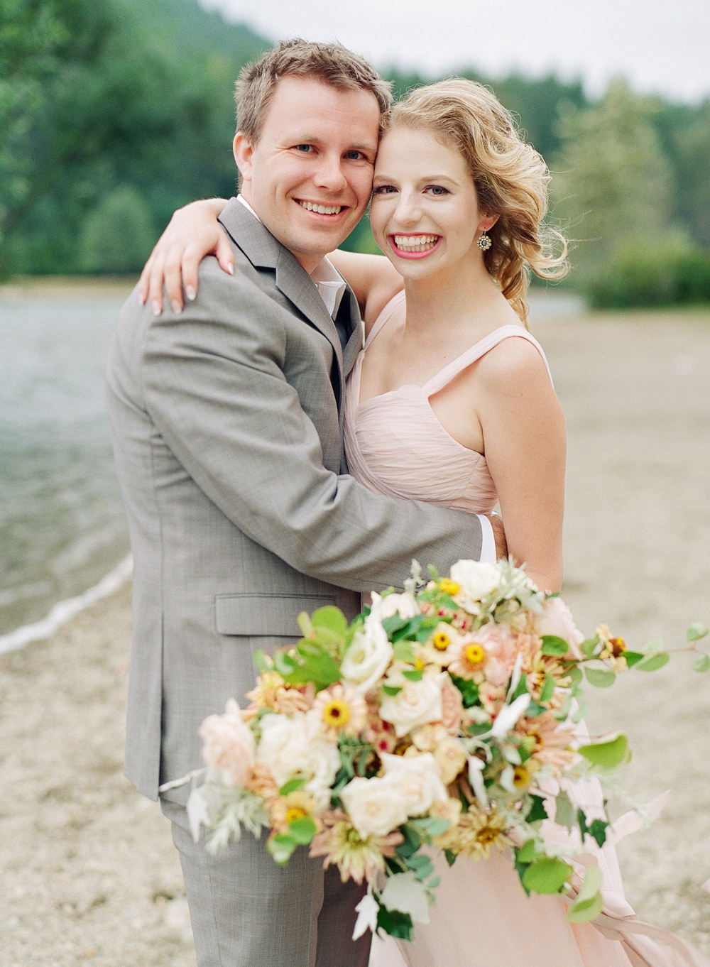couple hugging and holding white pink yellow green bouquet