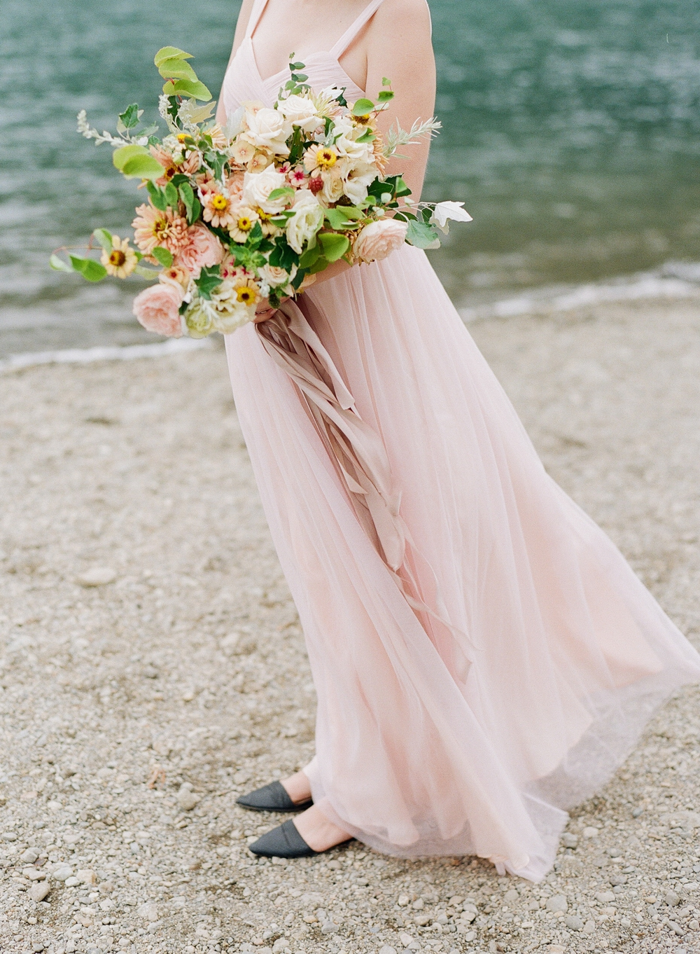 bride in blush pink dress holding white pink yellow and green bouquet