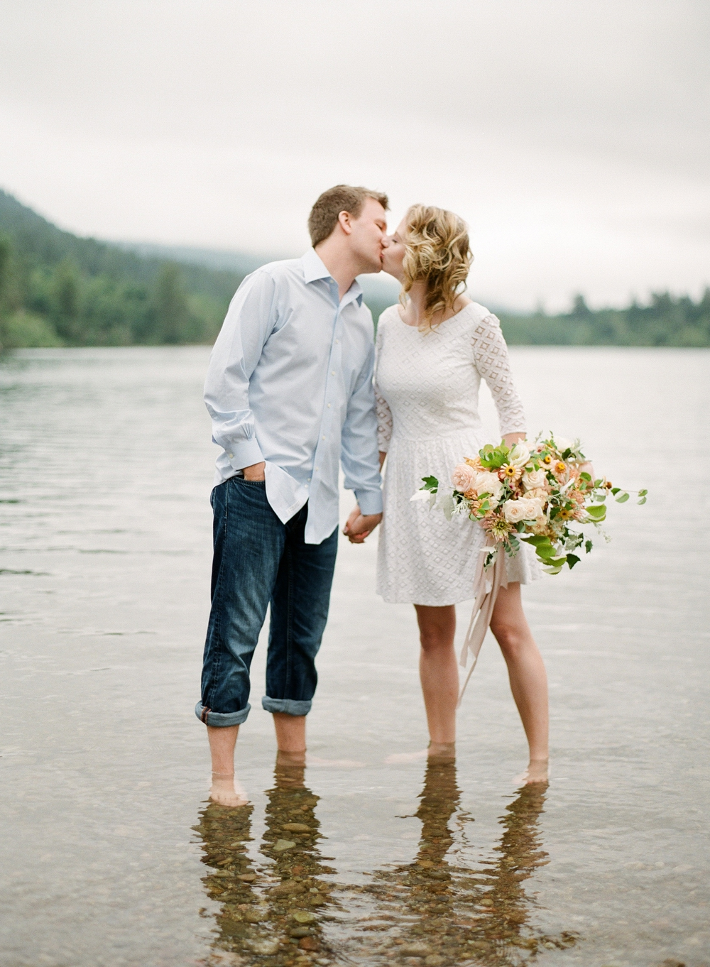 couple kissing standing in water woman in white eyelet dress holding white pink yellow and green bouquet