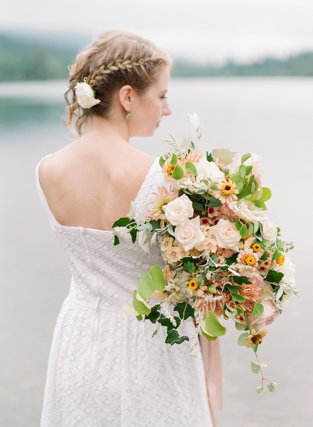 bride in white eyelet dress holding white pink yellow and green bouquet