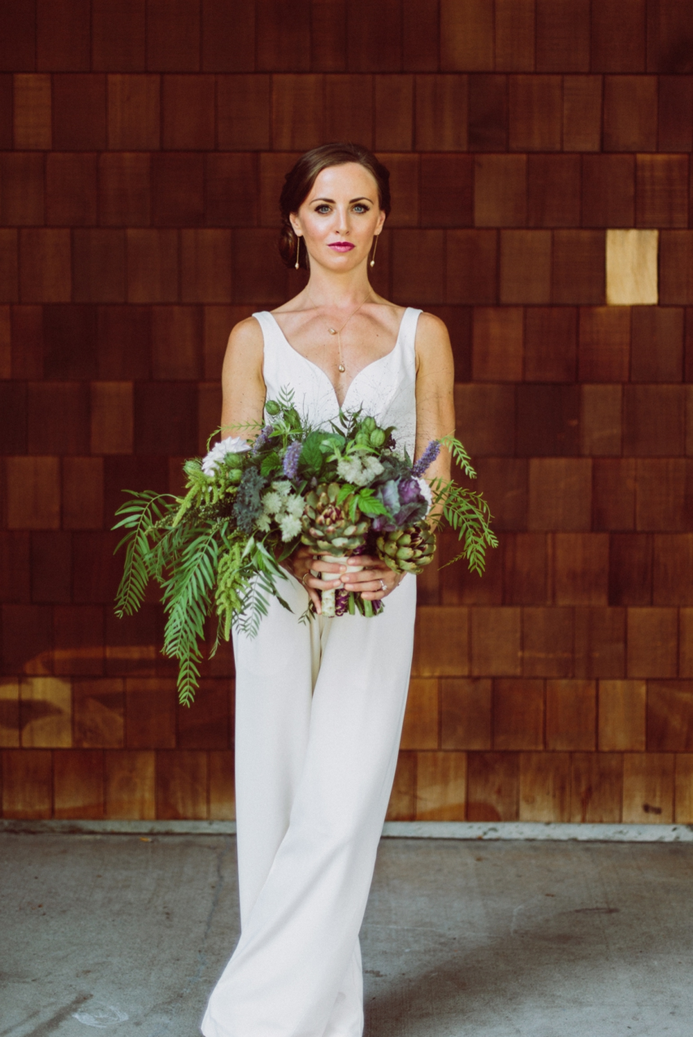 bride in white jumpsuit holding edible kale themed bouquet with herbs and berries