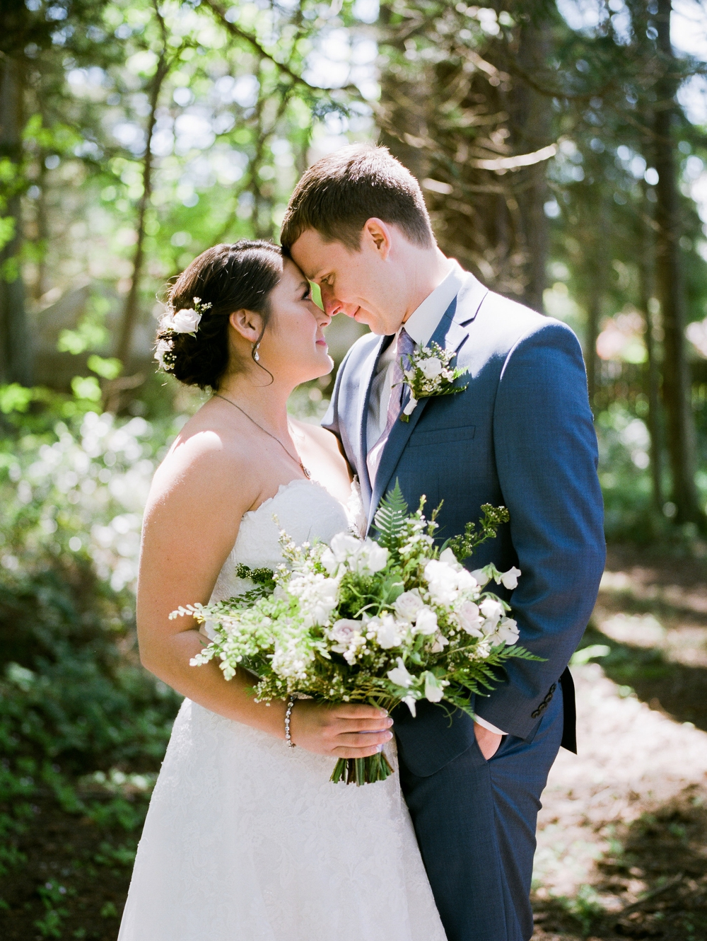 bride and groom nuzzling and holding a white spring themed bouquet