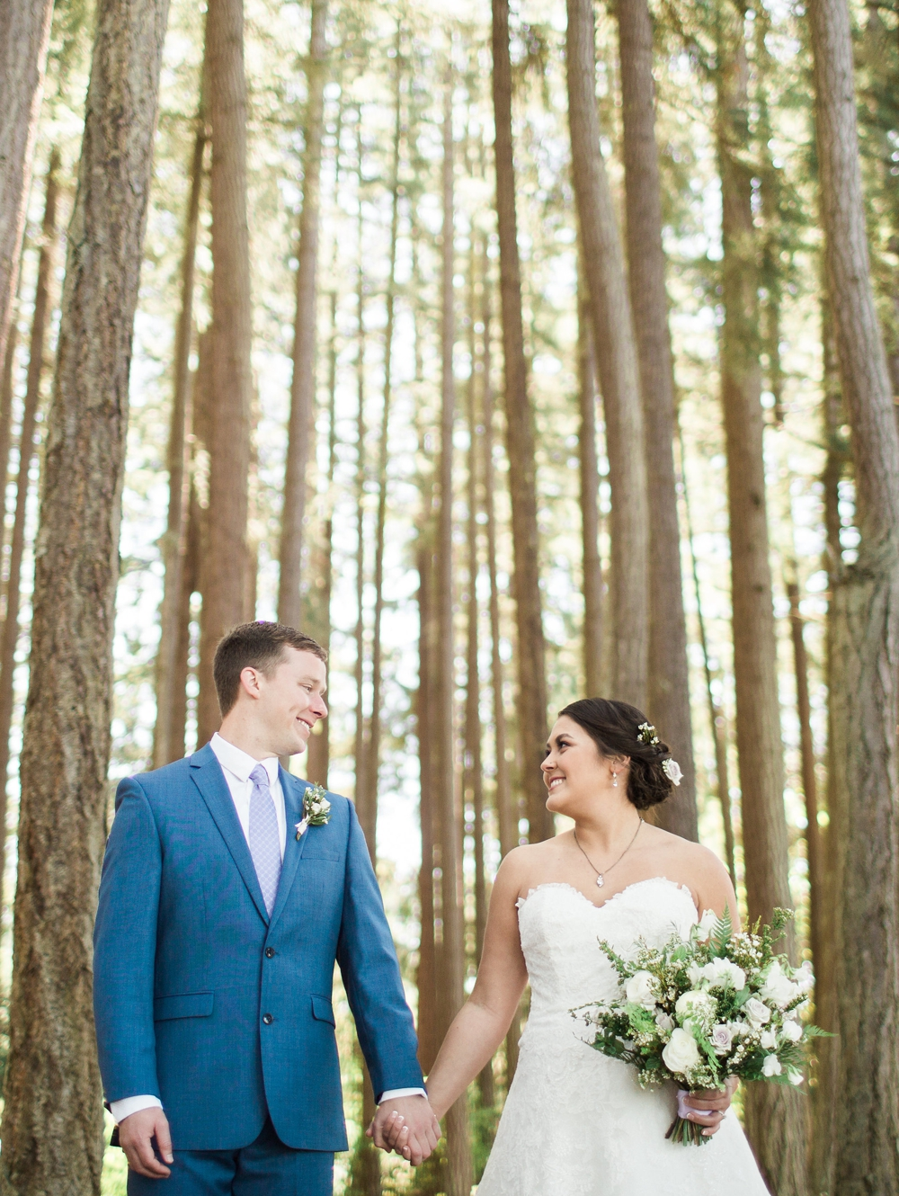 bride and groom holding hands and holding white bouquet in front of tall evergreen trees