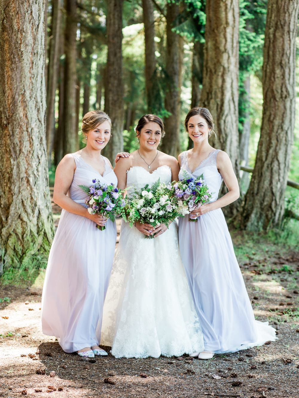 bride and brides maids in evergreen trees holding white and lavender spring bouquets