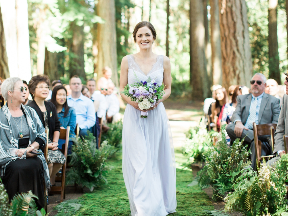 bride in lavender dress with spring bouquet walking down the ailse