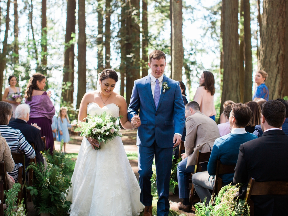 couple walking up the aisle with white spring bouquet in woods