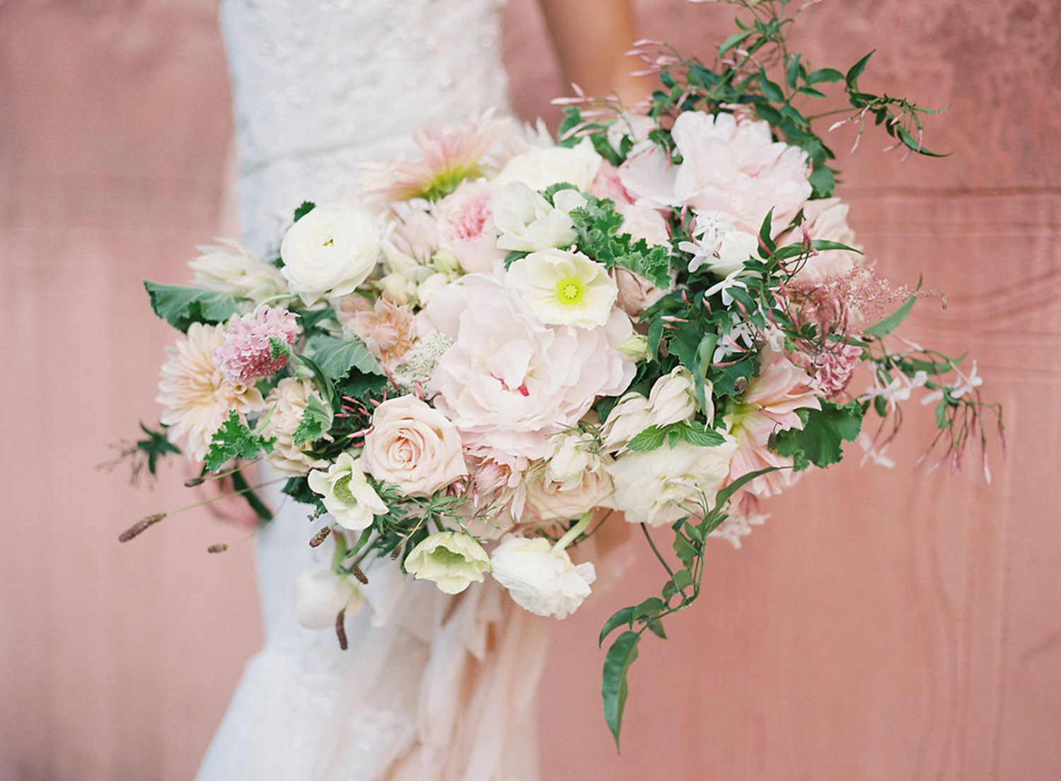 bride holding a white and pink bouquet standing against a pink wall in spring