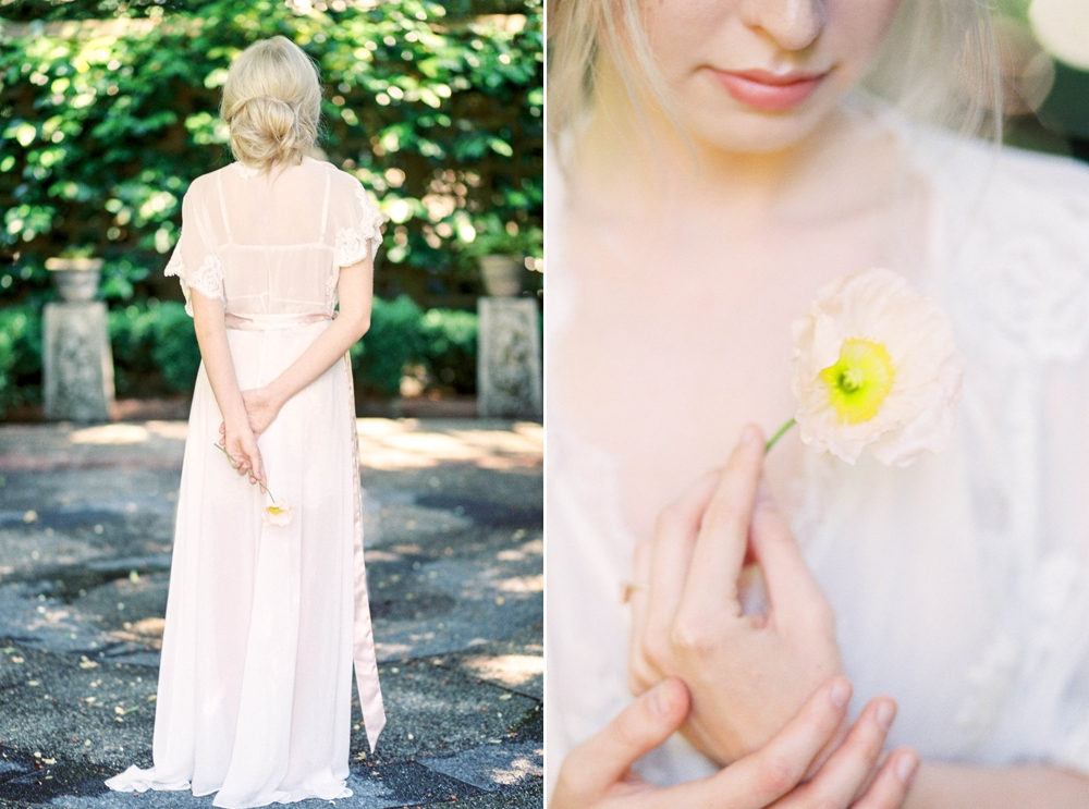 bride in lace dress holding a single pink flower