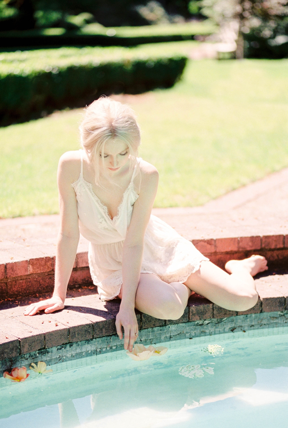 blonde woman in a white negligee lightly touching a flower floating in a fountain pool